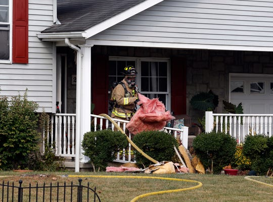 """A Lancaster firefighter tosses insulation out of a house Monday afternoon, Sept. 30, 2019, in the 2600 block of Heidelberg Drive in Lancaster. Firefighters were called to the house around 3:30 p.m. after the homeowner called 911 to tell dispatchers the her living room was on fire. When fire crews arrived, Assistant Chief K.J. Watts said they saw light smoke coming from the house. THey were able to put the small fire out. """"Most of the fire damage was contained to the living room, but there was extensive smoke damage,"""" Watts said, adding that the fire may have started by a candle. Pleasant Township Fire Department and Basil Joint Fire District firefighters assisted LFD at the scene."""
