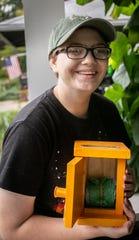 Cierra Haughton,18, presents her dog waste station box created using recycled plastic bags from newspapers to keep street clean in her Eastside neighborhood, Saturday, Sept. 28, 2019, Lansing, MI.