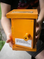 Cierra Haughton shows the outside of dog waste station box that stores repurposed plastic bags from newspapers to keep street clean in an Eastside neighborhood, Saturday, Sept. 28, 2019, Lansing, MI.