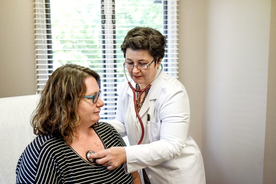 "Dr. Adriana Raus, right, listens to patient Jaime Cole's heart during an appointment on Monday, Sept. 30, 2019, at her Family Doc Direct office in Okemos. Raus practices what she calls ""direct primary care."" She doesn't take insurance and her patients pay her on a monthly basis instead of per-visit."