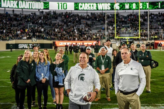 Michigan State's head coach Mark Dantonio, right, and basketball coach Tom Izzo watch a video piece on the big screen honoring Dantonio for becoming the most winningest coach in MSU history after the game on Saturday, Sept. 28, 2019, in East Lansing.