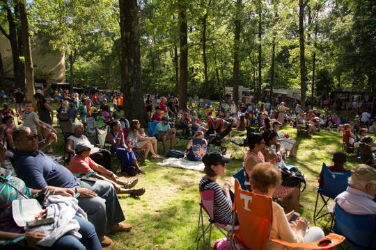 Attendees sit on the ground that will become The Grove at GPAC at a previous food truck festival hosted by the organization.