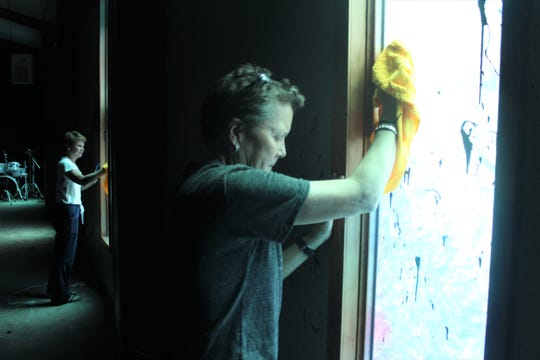 Beth Holloway cleans paint of the window at One Church Memphis on Sept. 30, 2019 after the church was vandalized over the weekend.