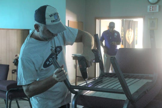 Jay Campbell drills the legs on chairs back together on Sept. 30, 2019, after One Church Memphis was vandalized over the weekend.