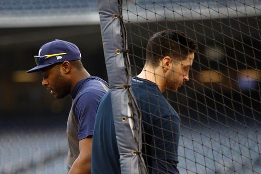 Lorenzo Cain walks past teammate Ryan Braun during batting practice Monday at Nationals Park. Both Cain and Braun are nursing injuries.