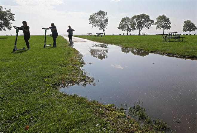 Scooter riders walked around a large puddle Monday rather than chance it as they rode along Milwaukee's lakefront in Veteran's Park. More rain is predicted on top of already saturated ground.