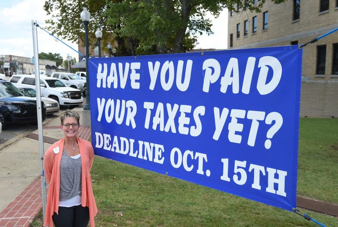 Baxter County Collector Teresa Smith stands next to a large sign on the county courthouse lawn reminding motorists that their property taxes are due later this month.