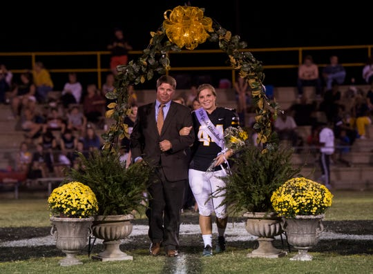 Autauga's Emma Wendland (44) is escorted by her dad, Andy, during the announcement of the homecoming court during halftime at Autauga Academy in Prattville, Ala., on Friday, Sept. 27, 2019. Autauga Academy defeated Tuscaloosa Academy 40-16.