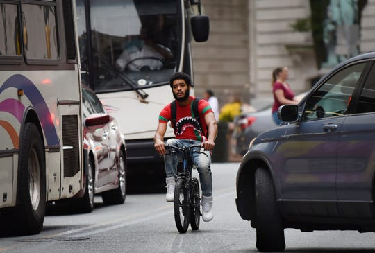 A young man rides a small bicycle in busy traffic in downtown Paterson on 09/39/19.