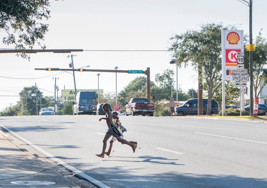 Children cross Cervantes Street between M Street and Pace Boulevard on Monday.