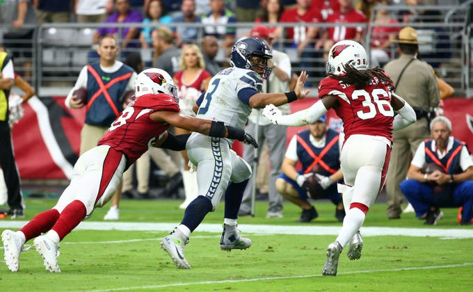 Seattle Seahawks quarterback Russell Wilson (3) carries the ball against Arizona Cardinals middle linebacker Jordan Hicks (58) and free safety D.J. Swearinger (36) in the second half during a game on Sep. 29, 2019 in Glendale, Ariz.