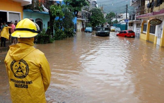 Un efectivo de Protección Civil trabaja este lunes en una zona afectada por la depresión Narda, en Puerto Vallarta (México).