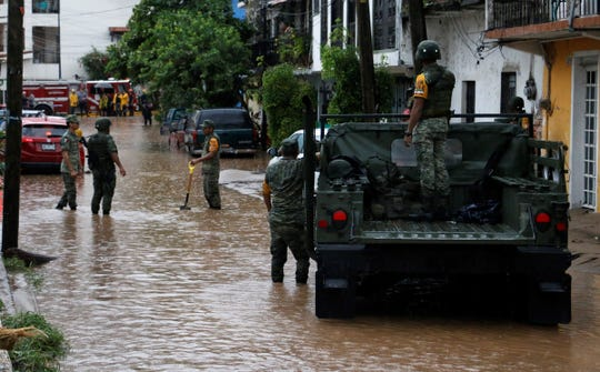Efectivos militares y de Protección Civil trabajan este lunes en las zonas afectadas por la depresión Narda, en Puerto Vallarta (México).