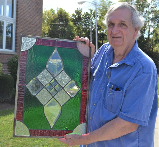 Ben Kendall holds one of his original, handmade stained glass works of art.