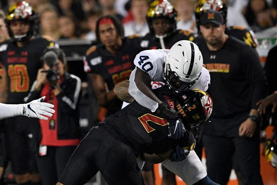 Penn State linebacker Jesse Luketa (40) tackles Maryland running back Lorenzo Harrison III (2) during the first half of an NCAA college football game, Friday, Sept. 27, 2019, in College Park, Md. (AP Photo/Nick Wass)