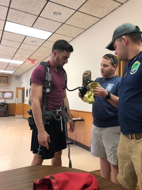 Albany basketball player Antonio Rizzuto puts on firefighting gear at the McKownville Fire Department. Rizzuto balances being a volunteer at the station with being a DivisionI student-athlete.