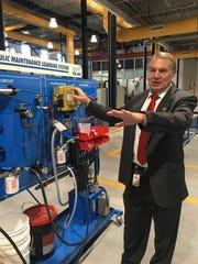 Dr. Russell Greenholt, superintendent of the Conewago Valley School District in Adams County, stands next to an Amatrol Hydraulics Learning System in the recently opened Colonial Career and Technology Center, a part of New Oxford High School.