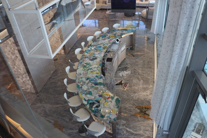 "The glass bar inside the Empathy Suite is actually a case stuffed with more than 100 pounds of medical debris. It's an art piece Damien Hirst calls ""Medical Waste."""