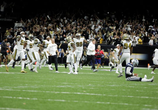 New Orleans Saints quarterback Drew Brees runs on the field in celebration with teammates as Dallas Cowboys quarterback Dak Prescott (4) sits on the ground after time expired at the Mercedes-Benz Superdome. The Saints defeated the Cowboys 12-10.