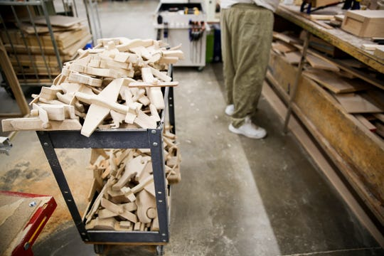 Wooden toy airplanes sit on a rolling cart in the carpentry workshop in Pheasantland Industries on Friday, Sept. 27, 2019.