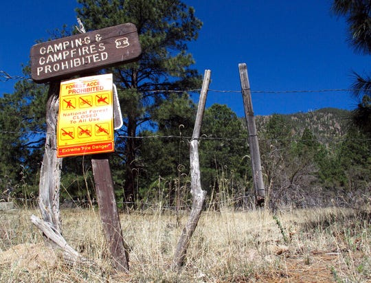 FILE - In a Thursday, May 24, 2018, file photo, a sign posted at a trail leads into the national forest in Flagstaff, Ariz.  Monsoon season carries high hopes for rain, thunder and lightning across the US Southwest, but it failed to deliver this year. Several communities in northern Arizona had the driest monsoon season on record, including Flagstaff. The season is characterized by a shift in wind patterns and moisture being pulled in from the tropical coast of Mexico. It runs from mid-June through September. (AP Photo/Felicia Fonseca, File)