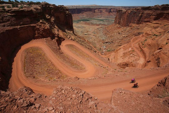 In this May 2013 photo mountain bikers near the end of their 75-mile trip as they make the steep climb on the Mineral Bottom Road after riding the White Rim Trail in Canyonlands National Park. ATVs will be allowed on certain roads in the five national parks in Utah under a new rule from the National Park Service that went through without public comment. (Francisco Kjolseth/The Salt Lake Tribune via AP)