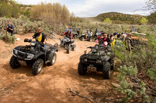 FILE - In this May 10, 2014, file photo, people ride ATV's into Recapture Canyon north of Blanding, Utah, in a protest against what demonstrators call the federal government's overreaching control of public lands. ATVs will be allowed on certain roads in the five national parks in Utah under a new rule from the National Park Service that went through without public comment. (Trent Nelson/The Salt Lake Tribune via AP, File)