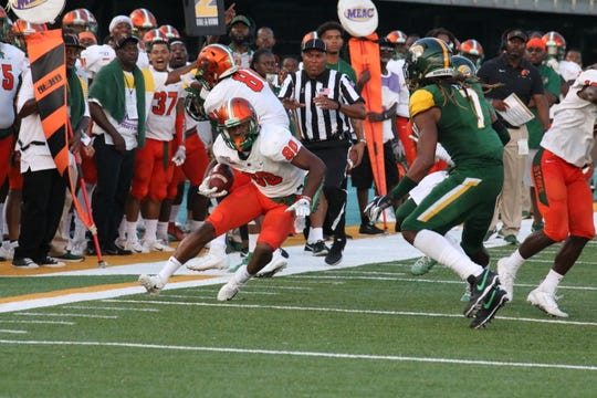 FAMU wide receiver Marcus Williams looks to dodge by Norfolk State defensive back Bobby Price.