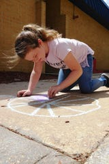 Sealey student Alanah Holmes draws a colorful peace symbol