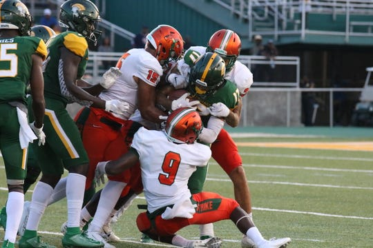 FAMU linebacker Elijah Richardson (15) and Patrick Bonner, Jr. (9) gang tackle Norfolk State wide receiver Tylan McElhenie.