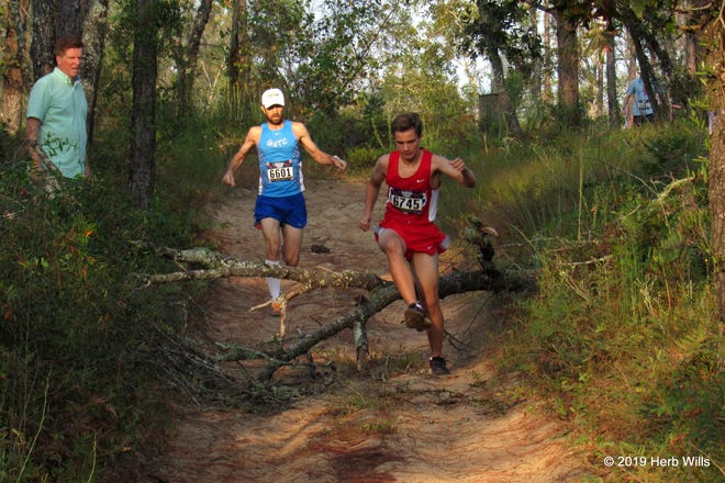 Paul Guyas and William Springer negotiate an obstacle during the 2019 Prefontaine Forest 5K.