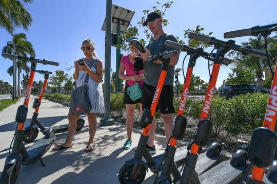 Sebastian residents (from left) Dee Lott, Tracie Hill, and husband Bill Hill, use their mobile phones to rent e-scooters on Sunday, Sept. 29, 2019, at the corner of Seaway Drive and A1A, across from Fort Pierce Jetty Park. Treasure Coast residents try out the new e-scooters located around downtown Fort Pierce, along Seaway Drive, and several Fort Pierce beaches. The electric scooter share program has 150 scooters deployed daily at designated locations. It costs $1 to unlock and rent, along with 15 cents per minute to ride. Operators need to be ages 18 and older to rent and ride, with a valid drivers license. The e-scooters will be available to ride from 7 a.m. to 9 p.m.