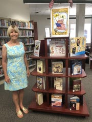 Daughters of  the American Revolution Regent Linda Gallup stands next to a display of books about the U.S. Constitution at the Susan Broom Kilmer Library in Fort Pierce.