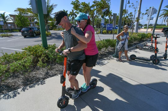 Sebastian residents Bill and Tracie Hill, try out an e-scooter as their friend Dee Lott, waits for rental authorization of a scooter on Sunday, Sept. 29, 2019, at the corner of Seaway Drive and A1A across from Fort Pierce Jetty Park. Treasure Coast residents try out the new e-scooters located around downtown Fort Pierce, along Seaway Drive, and several Fort Pierce beaches. The electric scooter share program has 150 scooters deployed daily at designated locations. It costs $1 to unlock and rent, along with 15 cents per minute to ride. Operators need to be ages 18 and older to rent and ride, with a valid drivers license. The e-scooters will be available to ride from 7 a.m. to 9 p.m.