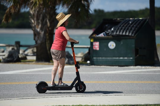Ana Herrada, of Vero Beach, rides an e-scooter on Sunday, Sept. 29, 2019, in the parking lot of Fort Pierce Beach. Treasure Coast residents try out the new e-scooters located around downtown Fort Pierce, along Seaway Drive, and several Fort Pierce beaches. The electric scooter share program has 150 scooters deployed daily at designated locations. It costs $1 to unlock and rent, along with 15 cents per minute to ride. Operators need to be ages 18 and older to rent and ride, with a valid drivers license. The e-scooters will be available to ride from 7 a.m. to 9 p.m.