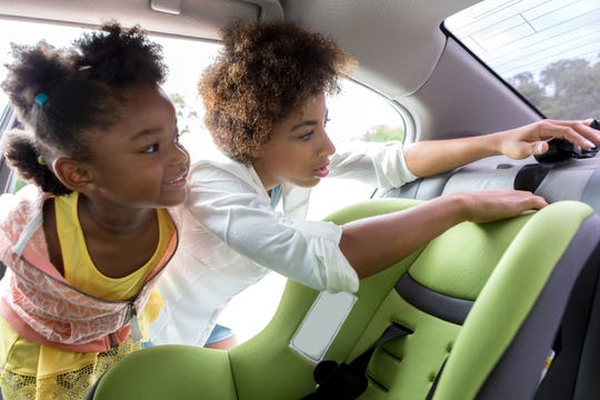 A  girl watches her mother as she tries to anchor a new car seat to the vehicle.