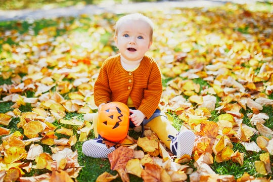 A young girl sits on the grass with a Halloween bucket and plays with leaves.