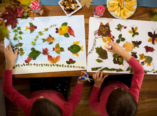 Two boys make art using leaves and glue