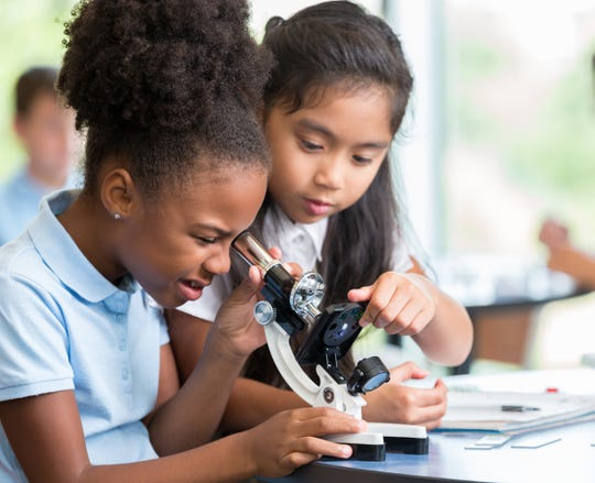 Two young girls look through a microscope and work on a science project together.