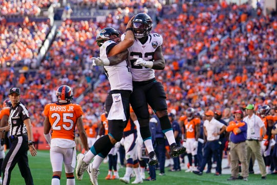 Jacksonville Jaguars running back Ryquell Armstead, right, celebrates with quarterback Gardner Minshew after scoring a touchdown during the second half of an NFL football game against the Denver Broncos, Sunday, Sept. 29, 2019, in Denver.