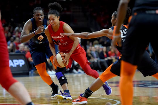 Kristi Toliver #20 of the Washington Mystics dribbles in front of Shekinna Stricklen #40 and Alyssa Thomas #25 of the Connecticut Sun during the second half of WNBA Finals Game One at St Elizabeths East Entertainment & Sports Arena on Sunday in Washington.