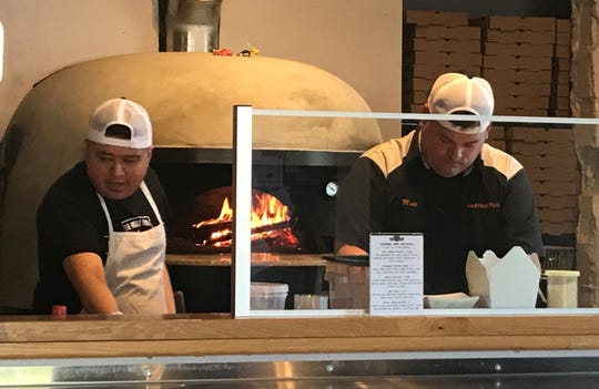 Patrons can watch their pizza bake at Wood Fired Pizza in Newark.