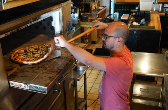 Steve Powell, owner of Argilla Brewing Co. @ Pietros Pizza cooks up deluxe pizza at his brewery restaurant on Kirkwood Highway in Newark.