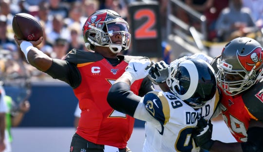 Jameis Winston throws a pass under pressure from Rams defensive tackle Aaron Donald.