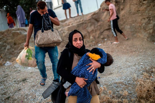 A woman carries a child during clashes with police outside the refugee camp of Moria on the Greek island of Lesbos on Sept. 29, 2019.