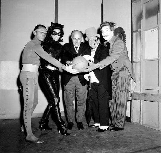 """Boston Celtics coach Red Auerbach (center) poses at the 1966 NBA Finals with the villains from """"Batman: The Movie"""": Frank Gorshin as the Riddler, Lee Meriwether as Catwoman, Burgess Meredith as the Penguin, and Cesar Romero as the Joker."""