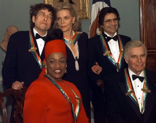 In 1997, at age 52, Norman became the youngest person ever to earn the Kennedy Center Honor at the time. The Honorees, standing from left are Bob Dylan, Lauren Bacall, and Edward Villella. Sitting, Norman and Charlton Heston. The recipients were honored by a dinner at the State Department on Dec. 6, 1997.