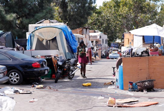A woman walks through a homeless encampment where presidential candidate and former Secretary of Housing and Urban Development Julian Castro visited in Oakland, California, on Sept. 25, 2019.