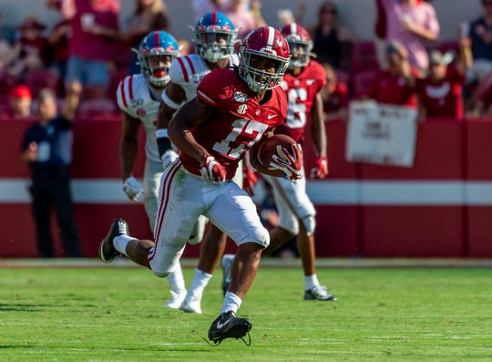 Alabama wide receiver Jaylen Waddle returns a punt against Mississippi during the first half at Bryant-Denny Stadium.