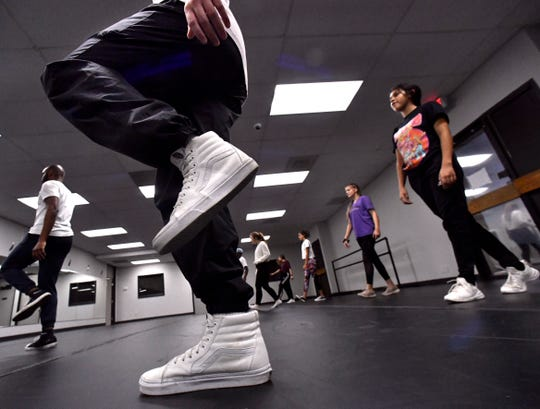 Dance students loosen up at the start of a class at Dance Discovery Studios on Sept. 25.